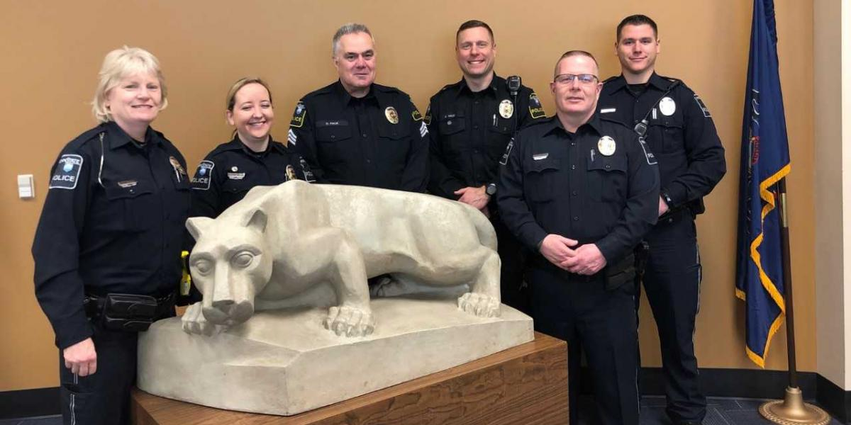 Officers stand next to Nittany Lion statue